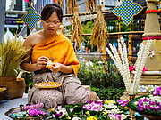 """08 APRIL 2017 - BANGKOK, THAILAND: A woman makes traditional Thai Songkran crafts at the """"Amazing Songkran"""" festival in Benchasiri Park in Bangkok. Songkran is celebrated in Thailand as the traditional New Year's Day from 13 to 16 April. Songkran is in the hottest time of the year in Thailand, at the end of the dry season and provides an excuse for people to cool off in friendly water fights that take place throughout the country. Songkran has been a national holiday since 1940, when Thailand moved the first day of the year to January 1. Songkran 2017 is expected to be more subdued than Songkran usually is because Thais are still mourning the October 2016 death of revered King Bhumibol Adulyadej.       PHOTO BY JACK KURTZ"""