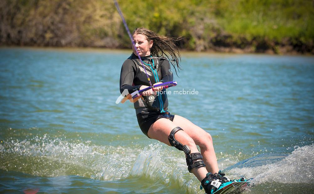 Female athlete wake boarding on the Snake River in Burley, Idaho.