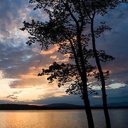 Maple trees are silhoutted against a sunset sky above Lake Winnepesauke.  Moultonboro Neck, Moultonboro, NH.