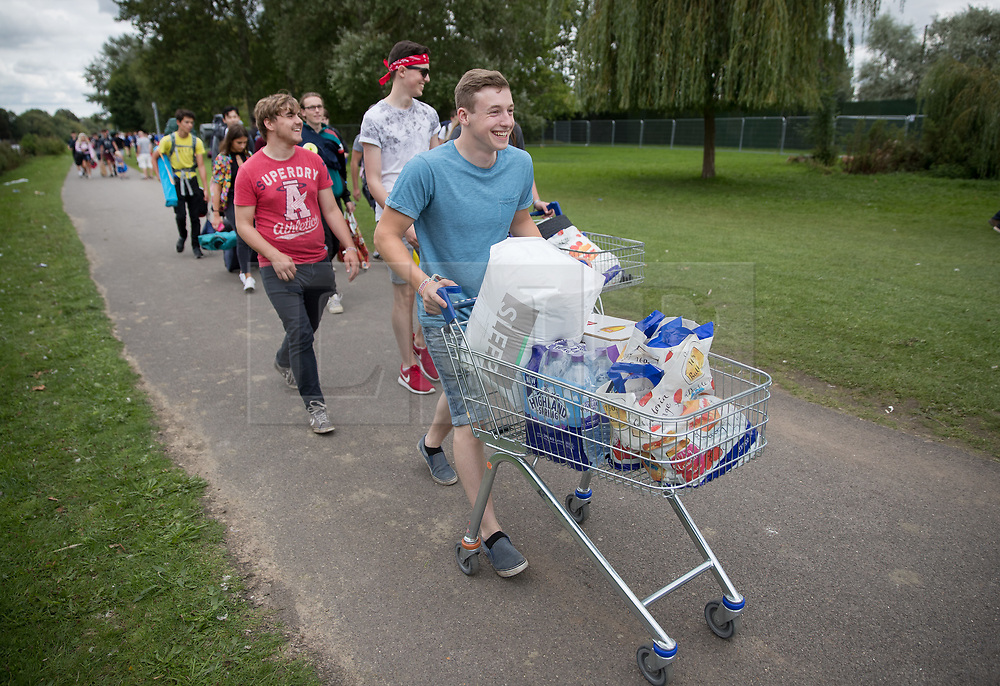 © Licensed to London News Pictures. 24/08/2017. Reading, UK. Music fans make their way to Reading Festival carrying their supplies in a shopping trolley. The weather is expected to stay fine for the start of the three day music festival. Photo credit: Peter Macdiarmid/LNP