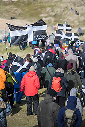 © Licensed to London News Pictures. 05/03/2017. PERRANPORTH, CORNWALL, UK.  Lots of St Piran's flags in the crowds. St. Piran's Day in Cornwall. St Piran is the patron Saint of Sinners in Cornwall and it is his flag that is recognised as the Cornish flag. Today his arrival from Ireland to Cornwall is celebrated across Cornwall especially in Perranporth where it is believed that he landed. He set up an Oratory and a Church the remains of which have been recently uncovered in the sand dunes at Perranporth..  Photo credit: MARK HEMSWORTH/LNP