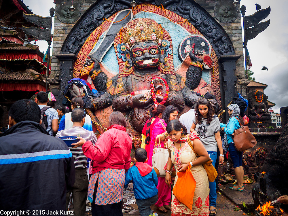 01 AUGUST 2015 - KATHMANDU, NEPAL:  People make offerings and pray at the shrine to Kal Bhairav, the Hindu deity of justice, in Durbar Square. Durbar Square was badly damaged in the 2015 Nepal Earthquake but has been reopened to tourists.     PHOTO BY JACK KURTZ