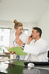 Doctor talking to nurse about medical record, Munich, Bavaria, Germany