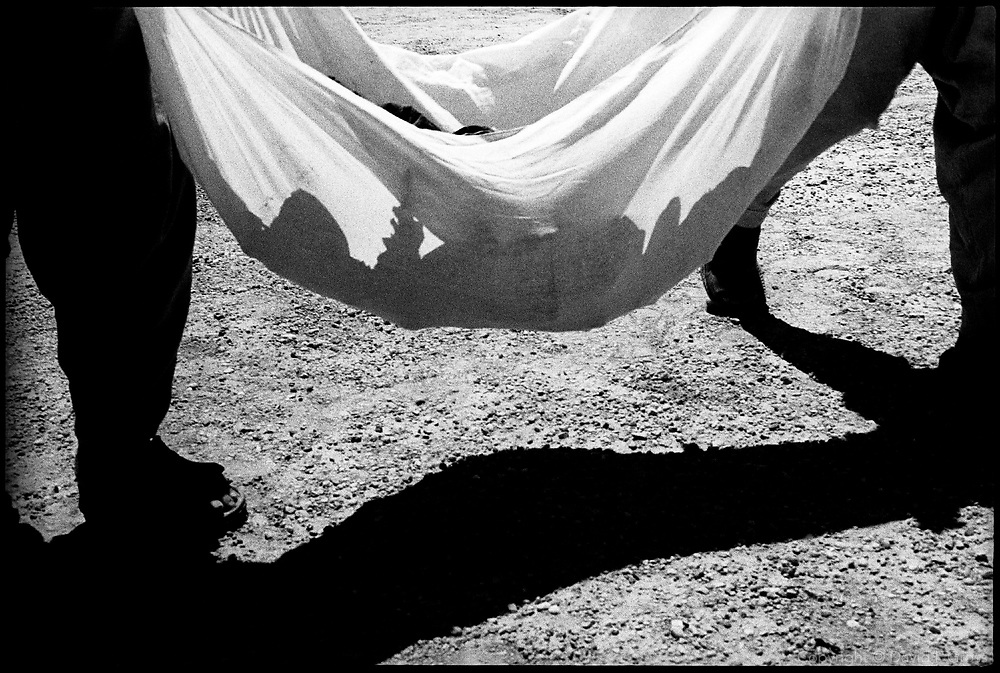 The Iraqi exhumation team carries another pile of bones in a shroud at a mass grave near Al-Musayab, Iraq, to be examined.