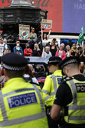 © Licensed to London News Pictures. 25/08/2021. London, UK. XR (Extinction Rebellion) protesters gather on Piccadilly Circus on a global day of action. XR are on day three of a planned two week protest in the captital calling for action on climate change. Photo credit: Peter Macdiarmid/LNP