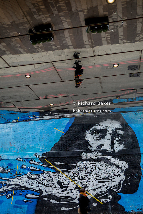 The face of a street art mural and mirrored passers-by, on 9th February 2017, in Shoreditch, London, England.