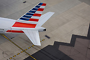 Aerial view (from control tower) of the tail of an American airliner at London Heathrow airport. The taxiing AA plane turns onto a directional centreline that helps pilots navigate to specific locations around the airport of five terminals on a site that covers 12.14 square kilometres (4.69 sq mi). London Heathrow is a major international airport, the busiest airport in the United Kingdom and the busiest airport in Europe by passenger traffic. It is also the third busiest airport in the world by total passenger traffic, handling more international passengers than any other airport around the globe.