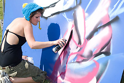 "Young woman spraypainting a wall at Nottingham University Student Union ""Sounds on the Downs"" Green Fields Festival; part of Green Week 2008,"