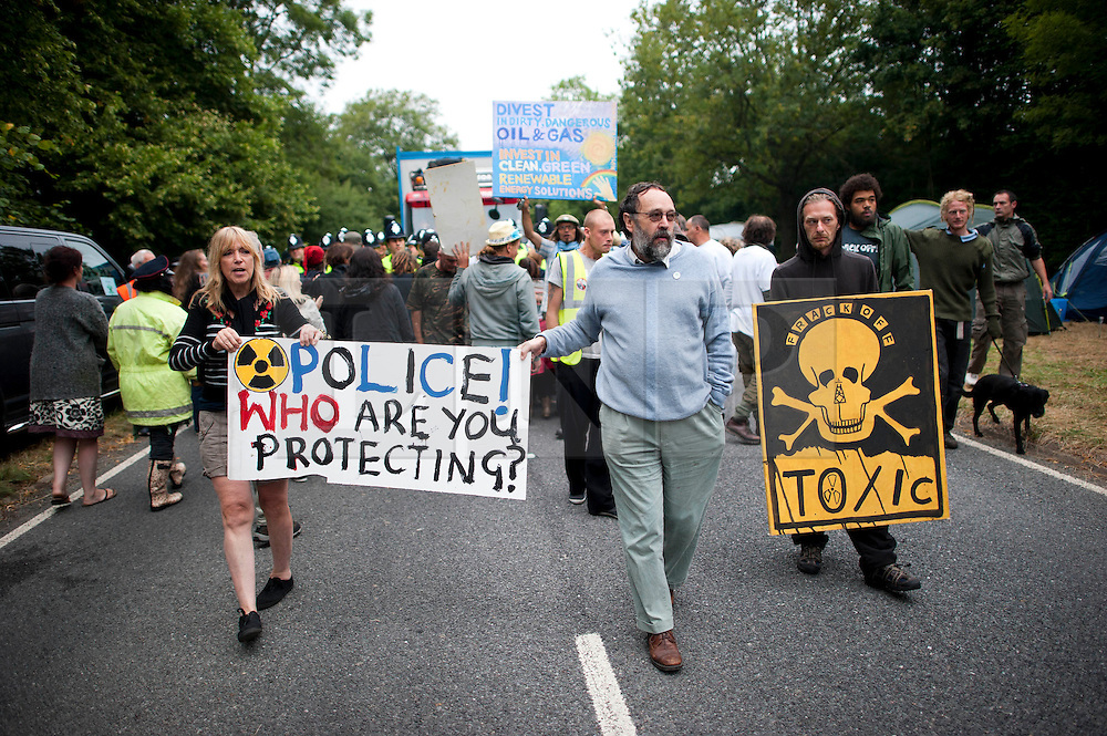 © London News Pictures. 16/08/2013. Balcombe, UK. Campaigners attempt to prevent a lorry entering the Cuadrilla drilling site in Balcombe, West Sussex which has been earmarked for fracking. Cuadrilla has temporarily ceased drilling at the site under advice from the police after campaign group No Dash For Gas threatened a weekend of civil disobedience. Photo credit: Ben Cawthra/LNP