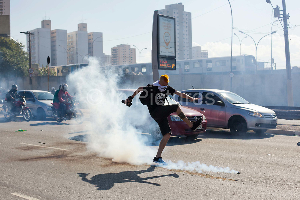 Proester kicks tear gas cannister. Members of the public were affected by the protests, when protesters tried to block the main highway going to Itauquera stadium, Police kept the traffic moving but fired tear gas, this endangered motorists, inlcuding a female scooter rider having btreathing problems due to the gas. Police clash with several hundred protesters in Sao Paulo, Brazil, using tear gas and stun grenades on the opening day of the FIFA World Cup 2014. There were some arrests and injuries inlcuding a CNN producer. The protesters were dispearsed relatively quickly due to the Brazilian Police's early show of force.