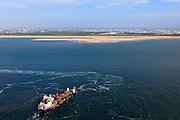 Nederland, Zuid-Holland, Gemeente Westland, 23-05-2011; Delflandse Kust ter hoogte van Ter Heijde en Monster, kassengebied van het Westland op het tweede plan. In de voorgrond  sleephopperzuiger verbonden met de persleiding die naar de kust loopt. Voor de kust in zee de Zandmotor: aanleg van kunstmatig schiereiland door het opspuiten van zand voor de kust. Wind, golven en stroming zullen het zand langs de kust verspreiden waardoor breder stranden en duinen ontstaan. De zandmotor is een experiment in het kader van kustonderhoud en kustverdediging. In de achtergrond de kassen van het Westland..A trailing suction hopper dredger before the coast of Holland, connected to the discharge pipe that runs to the shore. Building of the Sand Engine, construction of artificial peninsula by the raising of sand for the coast of Ter Heijde (near the Hague, at the horizon). Wind, waves and currents will distribute the sand along the coast yielding wider beaches and dunes along the coastline. The Sand Engine is a experiment for coastal maintenance of coastal defense. In the background the Westland greenhouses..luchtfoto (toeslag); aerial photo (additional fee required).foto Siebe Swart / photo Siebe Swart