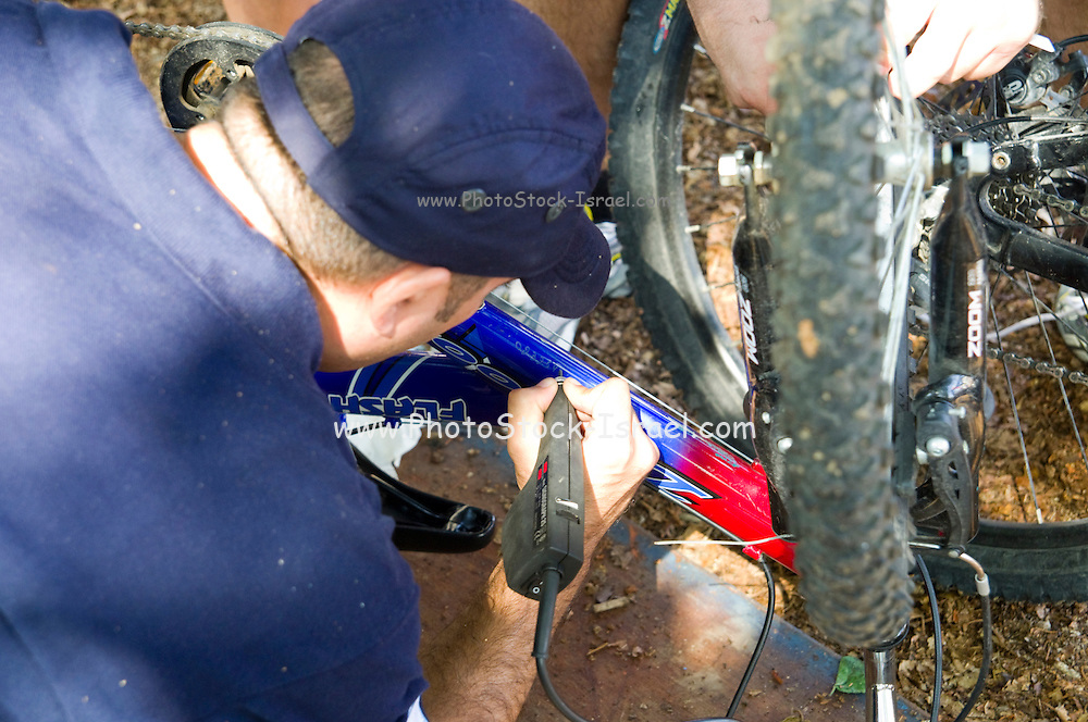 Israel,Tel Aviv, Israeli policeman marks a bicycle as a theft prevention measure by engraving a serial number onto the bike's frame
