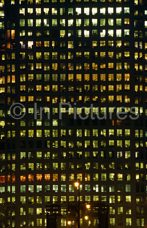 Canary Wharf tower seen through a telephoto lens from across West India Docks, London Docklands, East London England. We see dozens of office windows illuminated by individual green ambient light and in some windows, office workers can be seen at their desks. It is late in the working day but feverish business continues into the night. There is a strong graphic feel to the image, relying on the blank, unlit windows where other employees of their companies have left earlier and switched off their lights to save electric power. Canary Wharf is the product of the 1980s financial boom when during the office of Prime Minister Margaret Thatcher, huge building projects such as the Docklands consortium saw vast changes in London's landscape.