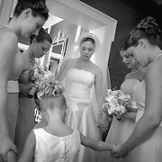 A bride and her bridesmaids gather for prayer just before the wedding ceremony on Kiawah Island in this black and white photograph. ©Travis Bell Photography