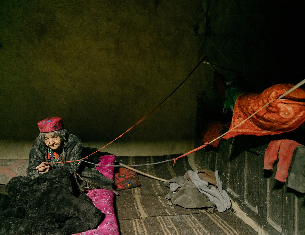 Grand mother pulling the string of a baby cot. House of Arif Baig.<br /> The traditional life of the Wakhi people, in the Wakhan corridor, amongst the Pamir mountains.