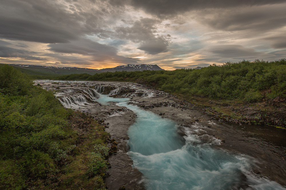 The river, Bruar, transforms into a beautiful waterfall, as Iceland's midnight sun slowly sets behind the mountains.  Glacial waters contain finely ground rocks, minerals, and sediments which refract the blue spectrum of the sun's light making the water appear blue.