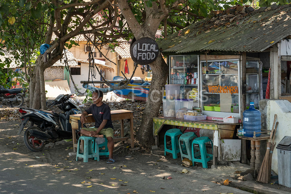 A man sits in the shade outside a local food stall at Batu Karas beach on the 31st October 2019 in Java in Indonesia.