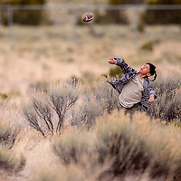 Mateo Loera tosses a football to his friends in Thoreau Friday.