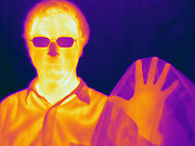 A man holding up a sheet of black plastic. This image has a corresponding visible light image.  This plastic is opaque to visible light, but is transparent to far-infrared light.  This is in contrast to the man's glasses which are opaque to the IR light.  This image was taken inthe far-infrared.  The different colors represent different temperatures on the object. The lightest colors are the hottest temperatures, while the darker colors represent a cooler temperature.  Thermography uses special cameras that can detect light in the far-infrared range of the electromagnetic spectrum (900?14,000 nanometers or 0.9?14 µm) and creates an  image of the objects temperature..