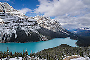 Snow covers the Waputik Range above turquoise Peyto Lake (1860 m or 6100 ft), in the Canadian Rockies, Banff National Park, Alberta. Bill Peyto was an early trail guide and trapper in the Banff area. Suspended rock particles of glacial rock flour create its bright  turquoise colour. Bow Pass (2068 m or 6787 ft) is the highest point on the Icefields Parkway, and a side road leads to a nature trail to Peyto Viewpoint (and higher bus road to wheelchair access). The lake is fed by Peyto Creek, which drains water from Caldron Lake and Peyto Glacier (part of the Wapta Icefield). Peyto Lake is the origin of the Mistaya River, which heads northwest. Banff National Park is Canada's oldest national park, established in 1885. Banff is part of the Canadian Rocky Mountain Parks World Heritage Site declared by UNESCO in 1984.