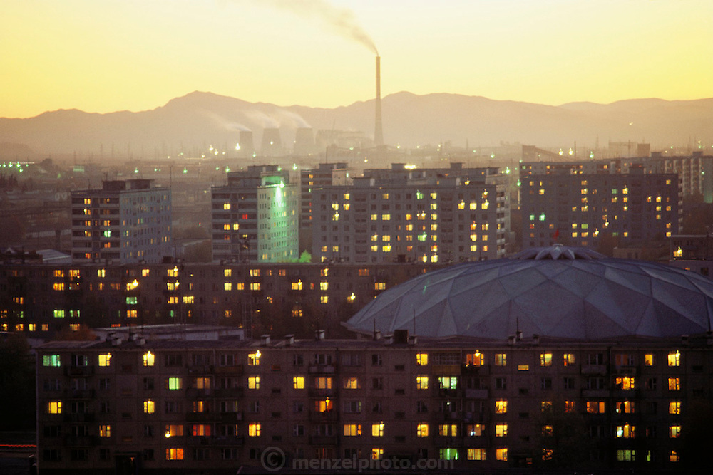 Russian style apartment buildings in urbanized Ulaanbaatar, Mongolia. The city's big coal-fired power plants (smokestack and 3 cooling towers in background) and countless small coal-burning stoves create a polluted haze. Published in Material World, page 43.