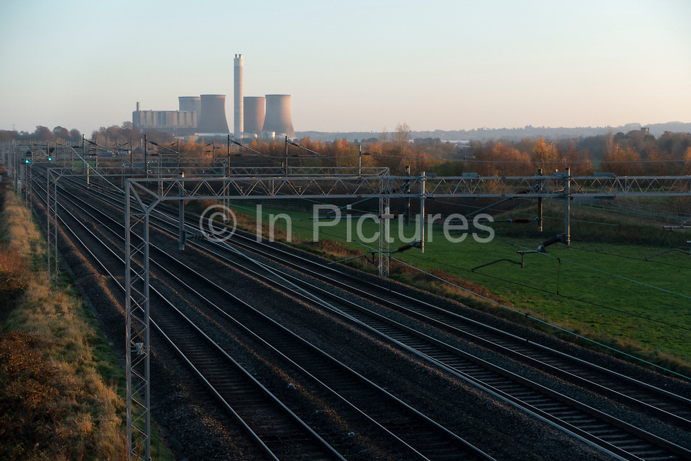 Countryside landscape along railway tracks towards the decomissioned Rugeley Power Station in Rugeley, Staffordshire, United Kingdom. The Rugeley power stations were a series of two coal-fired power stations located on the River Trent at Rugeley in Staffordshire. The first power station on the site, Rugeley A power station was opened in 1961, but has since been closed and demolished. Rugeley B power station was commissioned in 1970 and closed on 8 June 2016.