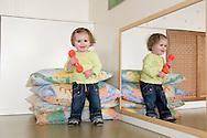 """Nederland, Herpen, 20090128...Kind met telefoon. Staat naast een spiegel...Kinderopvang 'Op de boerderij' in Herpen...""""OP DE BOERDERIJ"""" kinderopvang..is gevestigd bij een vleesveebedrijf te Herpen...Meisje met spiegelbeeld. spigel....Netherlands, Herpen, 20090128. ..Child with phone. Standing beside a mirror...Childcare on the farm in Herpen. ..""""ON THE FARM"""" childcare ..is located at a beef farm in Herpen...Girl with mirror image    .."""
