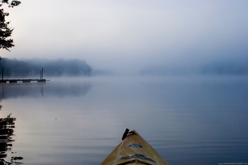 A Kayak cuts through the calm waters and morning mist, Trap Pond, Deleware.