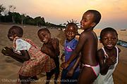 Children play at sunset on the shores of Likoma Island, Lake Malawi, Malawi.
