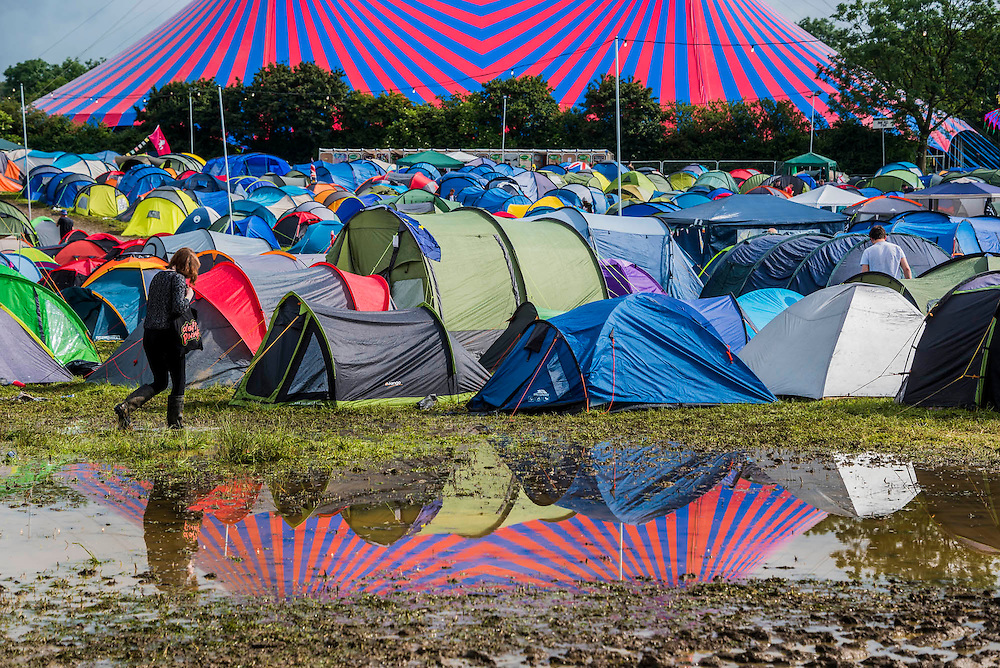 The John Peel tent and camping reflect in the water from the overnight downpoor- The 2016 Glastonbury Festival, Worthy Farm, Glastonbury.