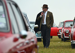 © Licensed to London News Pictures. 13/09/2013. Chichester, UK People enjoy the atmosphere at the 2013 Goodwood Revival. The event recreates the glorious days of motor racing and participants are encouraged to dress in period dress. The revival is the only event of its kind to be staged entirely in the nostalgic time capsule of the 1940s, 50s and 60s Photo credit : Stephen Simpson/LNP.