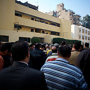 Egyptian men await the opening of the voting polls at El Tawfiya secondary school in Cairo's Shubra district.