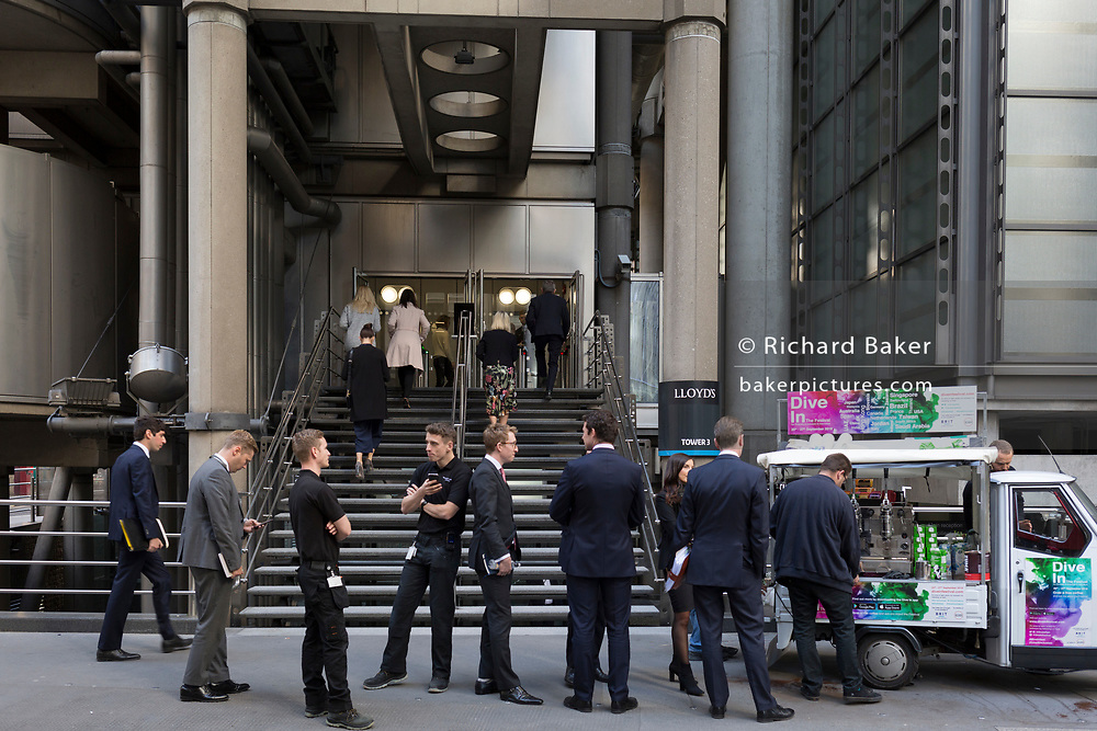 Businessmen and workmen queue for free coffee at the bottom of steps outside the headquarters of insurance brokers, Lloyds of London in Lime Street in the heart of the capital's financial district (aka The Square Mile), on 25th September 2018, in London, England.