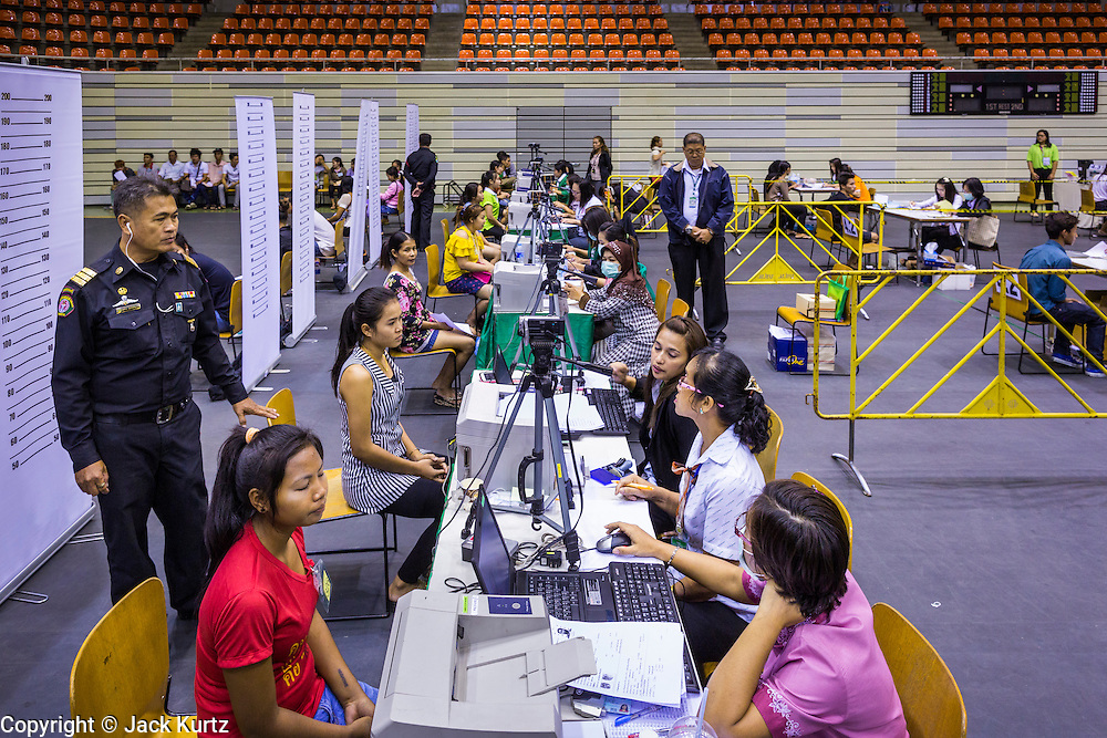 """17 JULY 2014 - BANGKOK, THAILAND: Thai immigration workers help undocumented Cambodian workers register for ID cards and work permits at the temporary """"one stop service center"""" in the Bangkok Youth Center in central Bangkok. Thai immigration officials have opened several temporary """"one stop service centers"""" in Bangkok to register undocumented immigrants and issue them temporary ID cards and work permits. The temporary centers will be open until August 14.    PHOTO BY JACK KURTZ"""