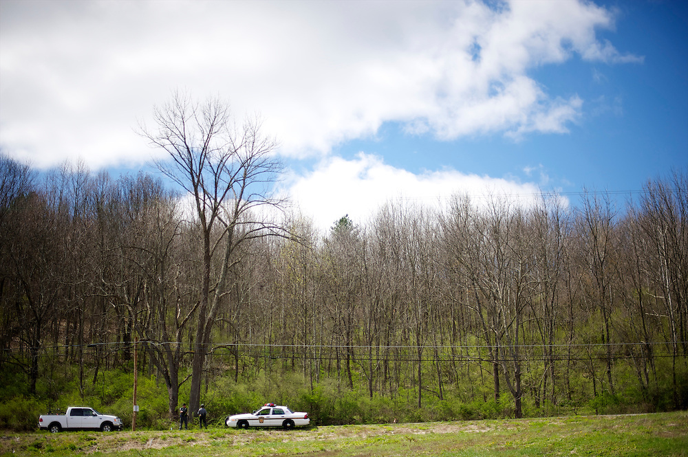 As a truck passes, Pennsylvania State Police monitor the road leading into Republican Presidential candidate Mitt Romney's rally at Mountain Energy Services in Tunkhannock, Pennsylvania on April 5, 2012.