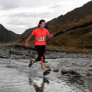 Runner Alex Martin crosses Moke Creek on the Ben Lomond High Country Station during the Pure South Shotover Moonlight Mountain Marathon and trail runs. Moke Lake, Queenstown, New Zealand. 4th February 2012. Photo Tim Clayton