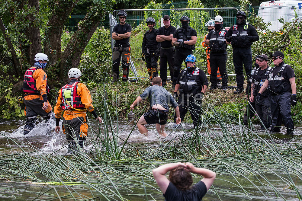 Police officers from Hampshire Police Marine Support Unit and enforcement agents from the National Eviction Team try to move a male environmental activist from HS2 Rebellion away from an ancient alder tree which he had been trying to protect from destruction during works for the HS2 high-speed rail link on 24th July 2020 in Denham, United Kingdom. A large security operation involving officers from the Metropolitan Police, Thames Valley Police, City of London Police and Hampshire Police as well as the National Eviction Team ensured the removal of the tree by HS2 despite the protests by activists.