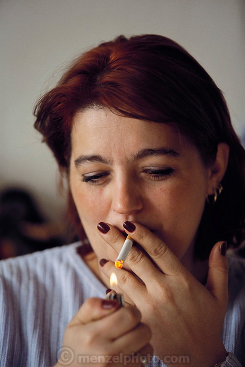 """Arina Demirovic's first cigarette of her chain-smoking day. Smoking is quite prevalent in Sarajevo. Though """"no smoking"""" signs abound, one can't see them through the smoke in most public places, Bosnia and Herzegovina. From coverage of revisit to Material World Project family in Sarajevo, Bosnia & Herzegovina, 2001. ©2005 Hungry Planet: What the World Eats"""