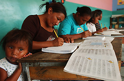 """Graceli Perez, 3, stands by as her mother, Adriana Perez,  and other students take part in Plan Robinson literacy classes in a small jungle village.  President Chavez aims to erradicate illiteracy in Venezuela through Plan Robinson,  which uses lessons and cassetes created in Cuba.  Critics of the program claim that the classes are primarily used as a tool of political indoctrination as part of Chavez's plan to """"Cubanize"""" Venezuela."""