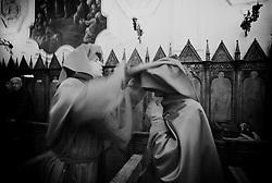 Reportage sulla processione del venerdi santo a Gallipoli...un confratello incappuccia un altro,  poco prima dell'inizio della processione