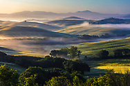 Picturesque Tuscany landscape of lush misty valley at morning