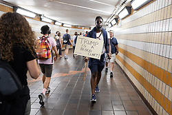 "© Licensed to London News Pictures . 13/07/2018. London, UK. A man carrying a "" Trump is a blood clart "" placard through Charring Cross Underground Station following a march to Trafalgar Square in protest against US President Donald Trump's UK visit . Photo credit: Joel Goodman/LNP"