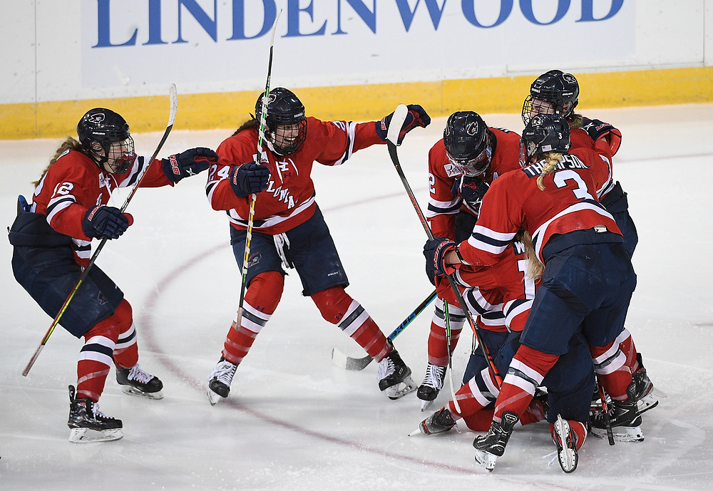 ERIE, PA - MARCH 05: Maggy Burbidge #9 of the Robert Morris Colonials celebrates with teammates after scoring the game winning goal in overtime to give the Colonials a 3-2 win over the Mercyhurst Lakers at the Erie Insurance Arena on March 5, 2021 in Erie, Pennsylvania. (Photo by Justin Berl/Robert Morris Athletics)