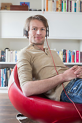 Portrait of man sitting on chair with headset and listening music, smiling