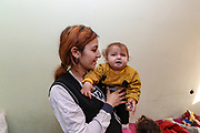 """A portrait picture of the Veronica and her 11 months child standing in the living room on Tuesday, Dec 28, 2020. They're now under Armenian government logistics support for food, shelter and other essential supplies. The family is living at an abandoned building of former """"SOVIET Hotel"""" in Metsamor without heating and water supply systems. The building is located near the Armenian Nuclear Power Plant, that is the only nuclear power plant in the South Caucasus, located 36 kilometres west of Yerevan in Armenia. (Photo/ Vudi Xhymshiti)"""