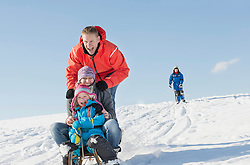Father, mother and daughter sledging down hill while son watching them, Bavaria, Germany