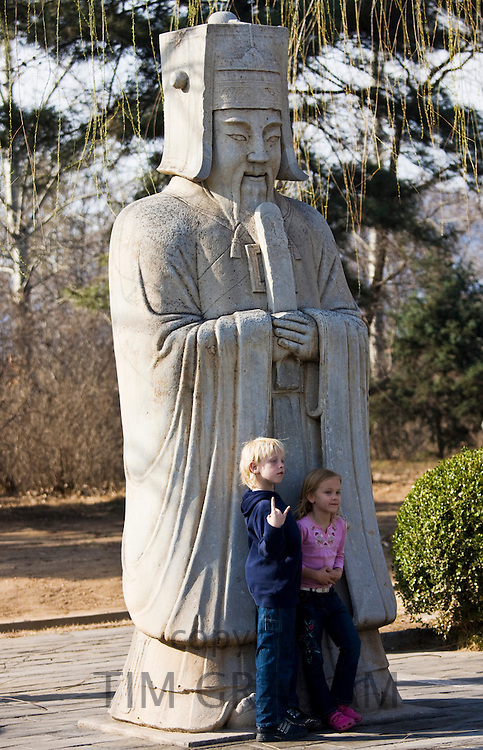 Children pose with statue of a high civil official, advisor to the emperor, on Spirit Way, Ming Tombs, Beijing, China