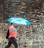A woman walks on a sidewalk next to an abandoned building on Western Ave. in South Bend on Monday.