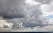 Heavy dark rain clouds pass over the land