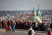 A group of tourists in front of the bell tower of St. Nicholas Church in Prague.